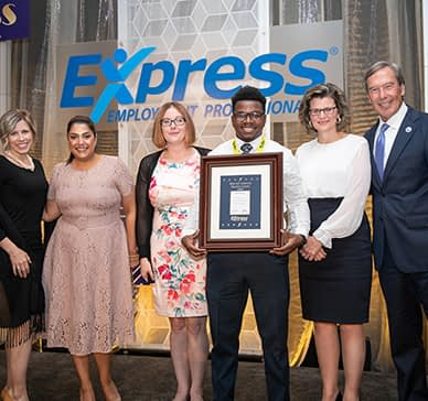 Group of Express employees in an Express location holding a plaque