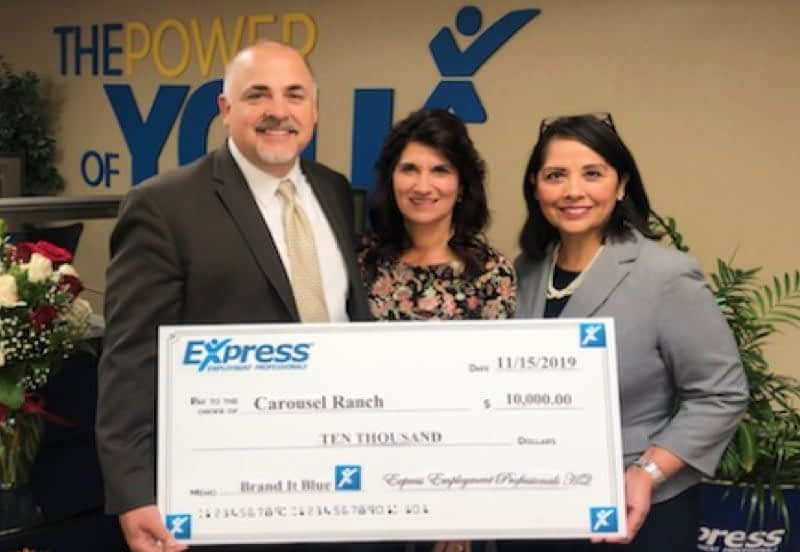 Three individuals standing proudly holding large donation check from Express
